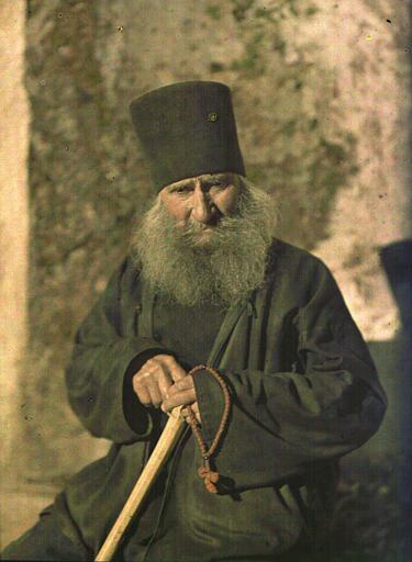 Religieux assis tenant un chapelet et un bâton