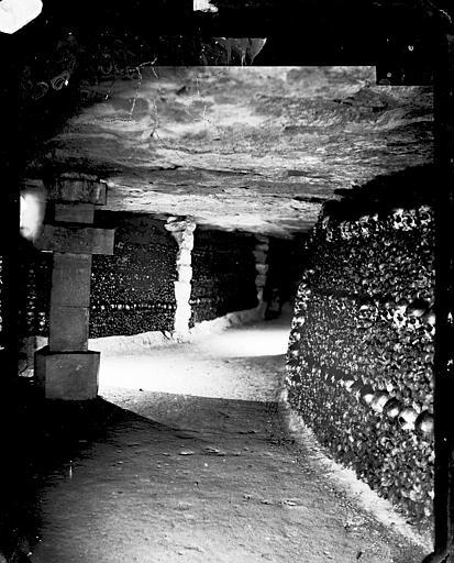 Vue intérieure d'une galerie : les murs recouverts d'agencements de crânes et d'os