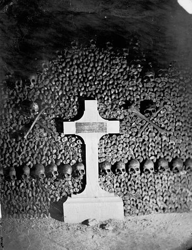 Vue intérieure d'une galerie : croix devant un mur paré d'os et de crânes