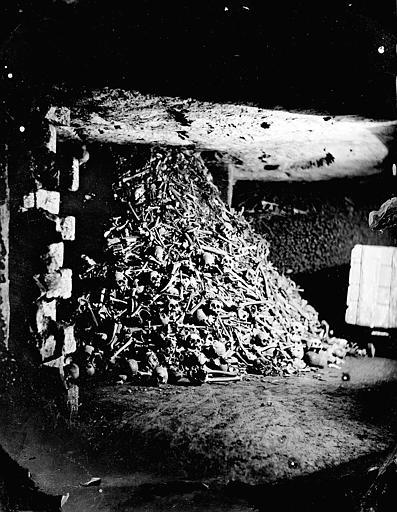 Vue intérieure d'une salle: entassements pêle-mêle d'os et de crânes