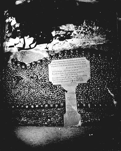 Vue intérieure d'une galerie: stèle devant un mur d'ossements