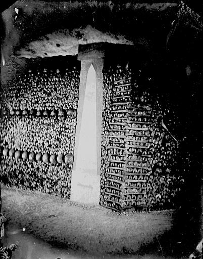 Vue intérieure : angle de galeries, murs parés d'ossements