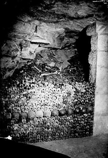Vue intérieure d'une galerie, mur d'ossements en cours de montage