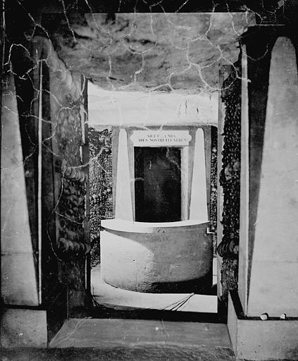 Vue intérieure : entrée d'une salle, couloir avec des murs d'ossements