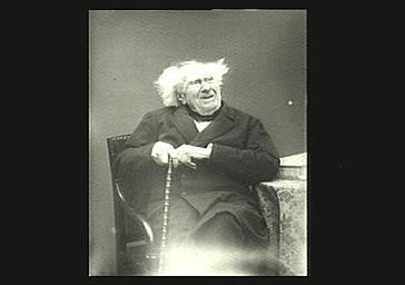 Chevreul assis près de la table, avec sa canne