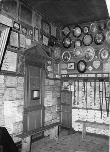Bas côté nord, fonds baptismaux du curé d'Ars encastrés dans le mur et fermés par une porte surmontée d'un fronton triangulaire, nombreux ex-voto de marbre et sous verre, 19e siècle