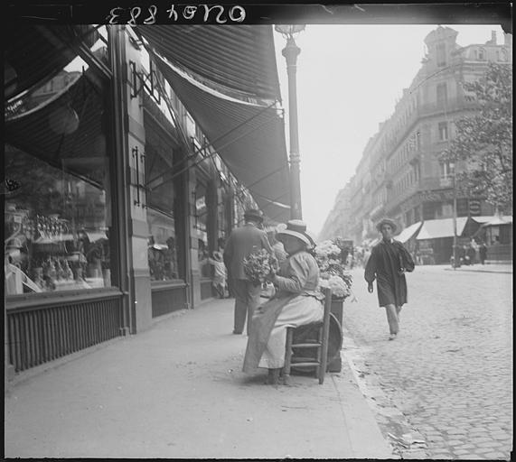 Scène animée : passants sur le trottoir, devantures de boutiques