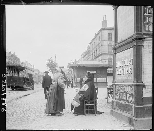 Scène animée : passants sur le trottoir, colonne Morris