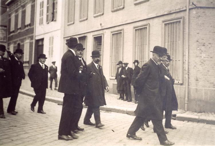 Bohain (Aisne), 1926, groupe d'industriels du textile défilant dans le cortège de la Saint-Louis, patron des tisseurs. De gauche à droite : MM : - inconnu, Deflandre (directeur du tissage du Vert Muguet) ; Tavernier (dessinateur en tissus) ; Roger Noiret (fils du directeur A. Noiret) ; Desprez (directeur du tissage Baboin) ; Poirier (directeur des ateliers Gadel) ; 3 inconnus sur le trottoir ; Constant Colard (directeur du tissage Thabut) ; Charles Gadel ; Arthur Noiret (directeur du tissage Noiret)