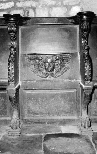 Stalle en bois sculpté ornée d'un motif de tête d'ange sur le dossier et de végétaux stylisés sur les côtés, 16e siècle, vue de face