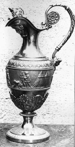 Burette de Monseigneur Pons sur le thème de l'eau, argent, 19e siècle, vue du côté gauche, avec au sommet du couvercle un coquillage en ronde bosse, et sur la panse la scène des hébreux trouvant de l'eau dans le désert suite au frappement du rocher par Moïse