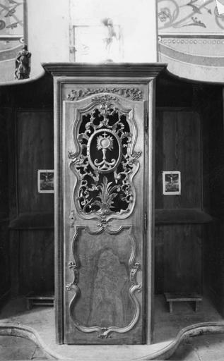 Confessionnal, bois sculpté, époque Louis XV, au centre panneau ajouré présentant des rinceaux végétaux encadrant un motif de gloire