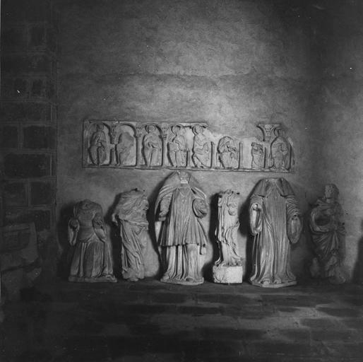 Dépôt lapidaire, sculptures fragmentaires : restes d'un linteau avec des personnages assis sous des arcades et différents corps acéphales