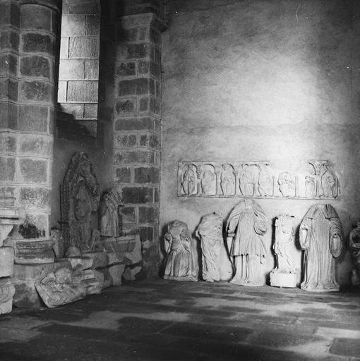Dépôt lapidaire, sculptures fragmentaires : restes d'un linteau avec des personnages assis sous des arcades lors d'un jugement dernier et différents corps acéphales , vus par la droite