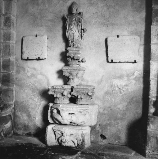 Dépôt lapidaire, sculptures fragmentaires : statue de saint évêque présentée au sommet d'une pile de fragments de chapiteaux sculptés, encadrée par deux plaques gravées