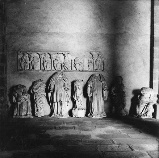 Dépôt lapidaire, sculptures fragmentaires : restes d'un linteau avec des personnages assis sous des arcades lors d'un Jugement Dernier, et différents corps acéphales