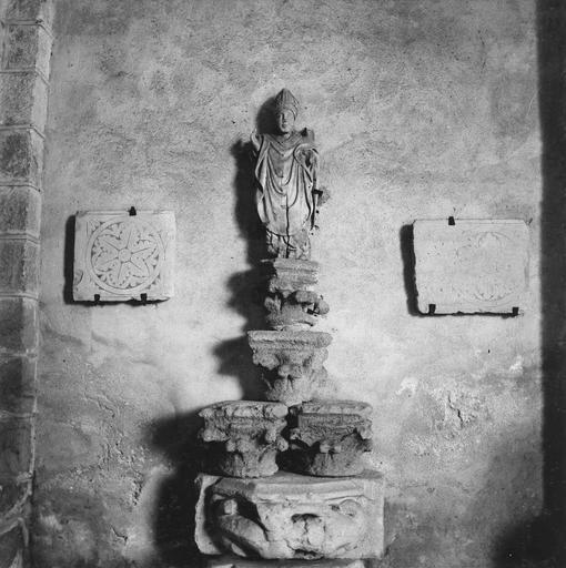 Dépôt lapidaire, sculptures fragmentaires : statue de saint évêque présentée au sommet d'une pile de fragments de chapiteaux sculptés, encadrée par deux plaques gravées, placée côté Sud de la salle