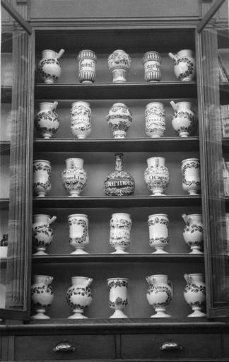 Ensemble constitué de cinquante pots à pharmacie en faïence de Nevers pour la majorité, 17e siècle, présenté dans le second placard comprenant cinq étagères