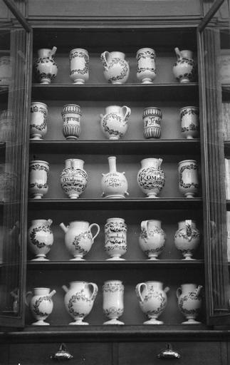 Ensemble constitué de cinquante pots à pharmacie en faïence de Nevers pour la majorité, 17e siècle, présenté dans le premier placard comprenant cinq étagères