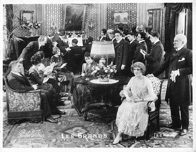 Réunion dans un salon tandis qu'un personnage est au piano à l'arrière plan dans 'Les Grands' de Georges Denola (Pathé,SCAGL)
