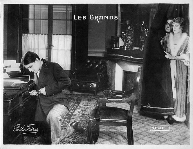 Un homme, observé par un couple caché derrière un rideau, force un tiroir de bureau dans 'Les Grands' de Georges Denola (Pathé,SCAGL)