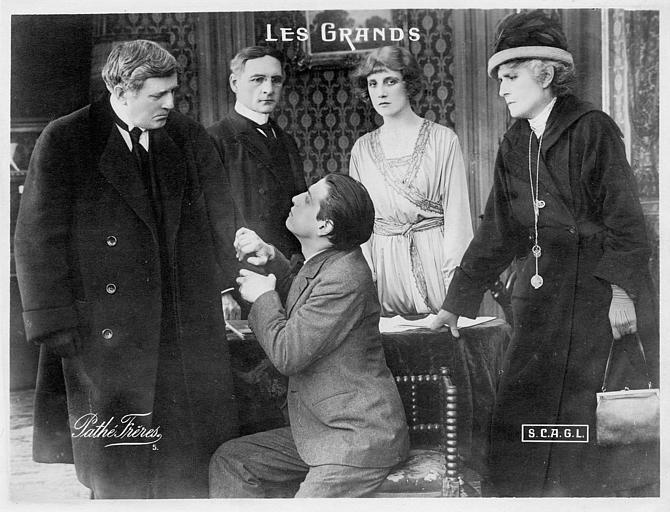Un homme s'accroche au bras d'un autre entouré de trois personnages dans 'Les Grands' de Georges Denola (Pathé,SCAGL)
