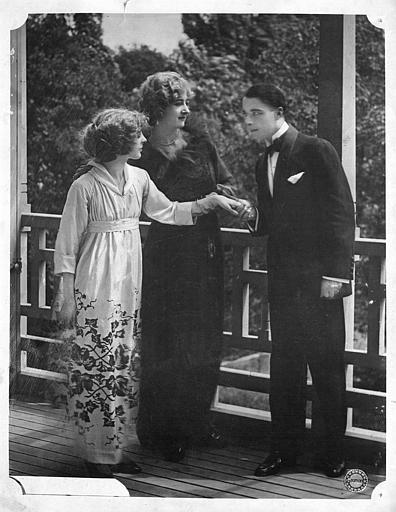 Sur un balcon, un homme tient la main d'une femme en compagnie d'une troisième  (Gaumont)