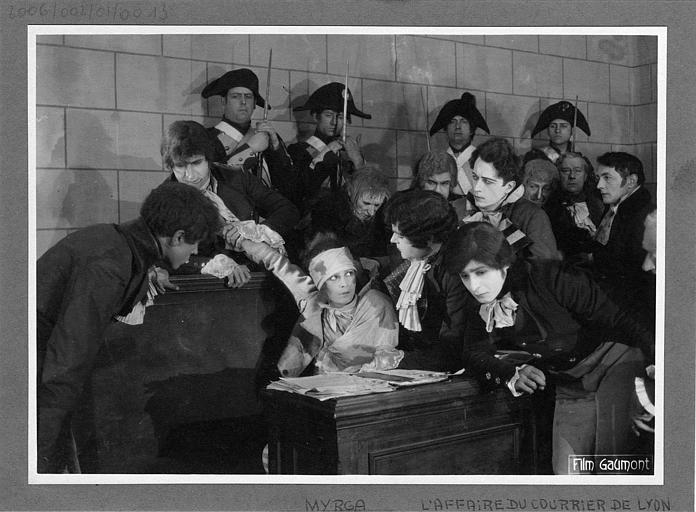 Scène dans un tribunal à l'époque révolutionnaire, des personnages debout entourent une femme assise qui est blessée à la tête : Laurence Myrga dans 'L'affaire du courrier de Lyon' de Léon Poirier (Gaumont)