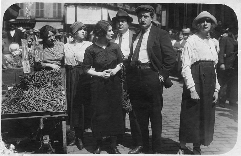 Personnages au milieu d'une rue pavée près d'une charrette de maraîcher avec des haricots 'sans fil'