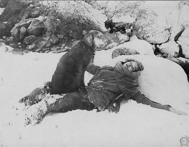 Laurence Myrga allongée dans la neige avec un chien (Gaumont)
