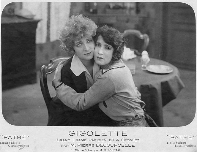 Séphora Mossé dans le rôle de Zelie Vauquelin et Elaine Vernon dans celui de Geneviève ou Marie, joue contre joue, sont assises sur la même chaise dans 'Gigolette' de Pierre Decourcelle et H. Pouctal (Pathé)