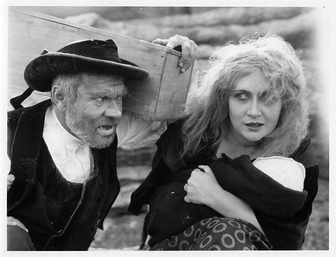 Gil Clary interprète Louise Lardic portant un bébé aux côtés d'un homme portant une caisse en bois sur l'épaule dans 'Les fiançailles rouges' de Roger Lion (Roger Lion)