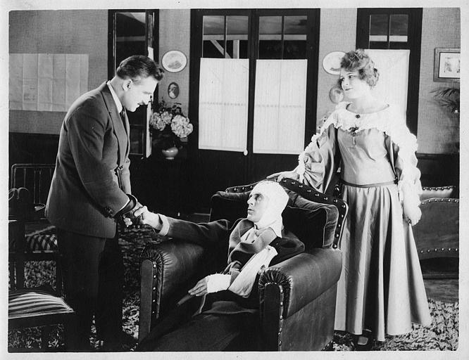 Un homme blessé dans un fauteuil entouré d'un homme qui lui serre la main et d'une femme  (Dal Film)