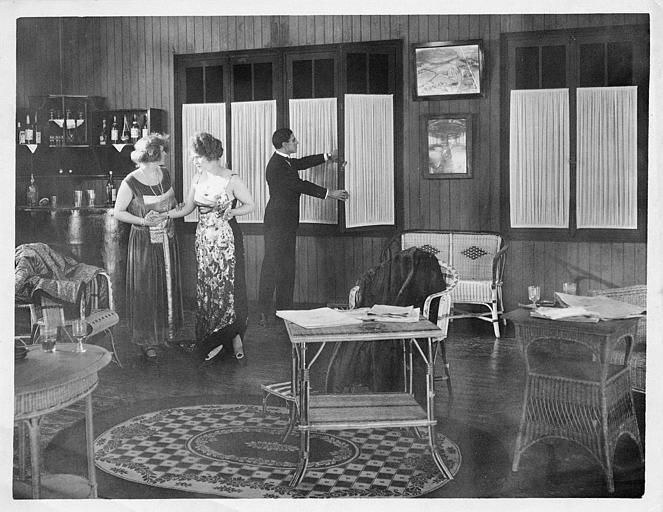 Dans un salon, deux femmes et un homme fermant la fenêtre (Dal Film)