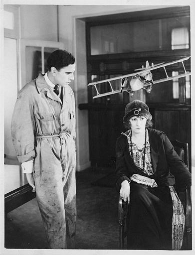 Une femme assise à côté d'un homme en tenue de mécanicien debout, devant une maquette d'avion à l'arrière plan (Dal Film)