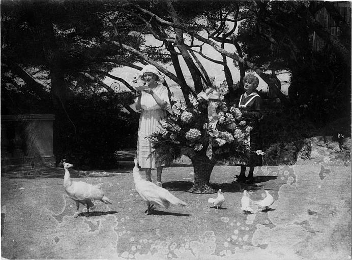 Dans un jardin, devant une grosse corbeille de fleurs, une femme lit une lettre en présence d'une domestique : Gaby Deslys dans 'Le Dieu du hasard' d'Henri Pouctal
