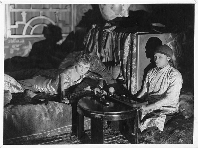 Une femme allongée sur le ventre fumant de l'opium et une enfant dans un salon orientalisant