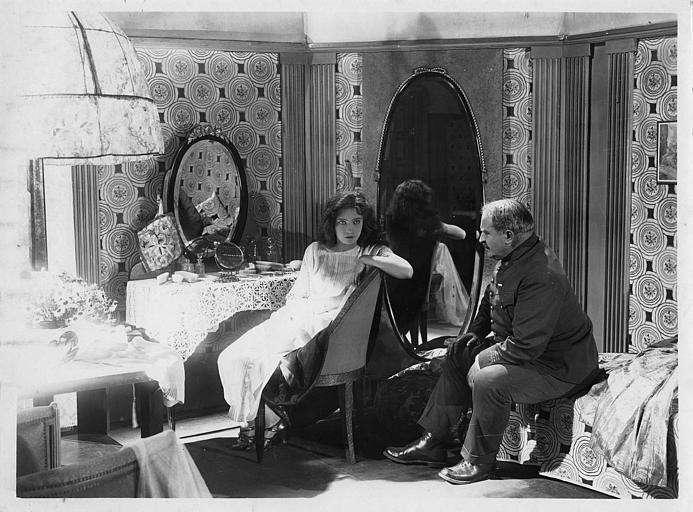 Dans une chambre, Henri Etiévant en uniforme et Choura Milena devant sa coiffeuse dans 'La châtelaine du Liban' de Marco de Gastyne