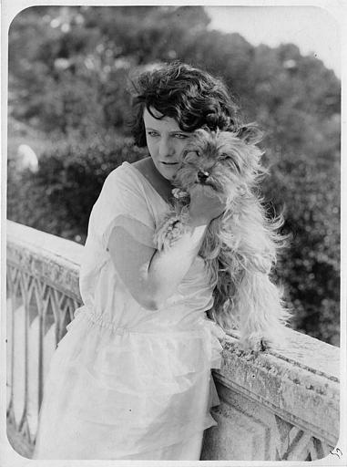 Une femme tenant un chien près d'une rambarde en ciment