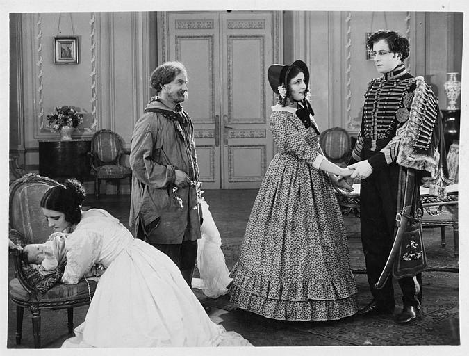 Quatre personnages dont Hélène Darly, qui joue Marie Didier, et un bébé dans un salon dans 'Le chiffonnier de Paris' de Serge Nadejdine