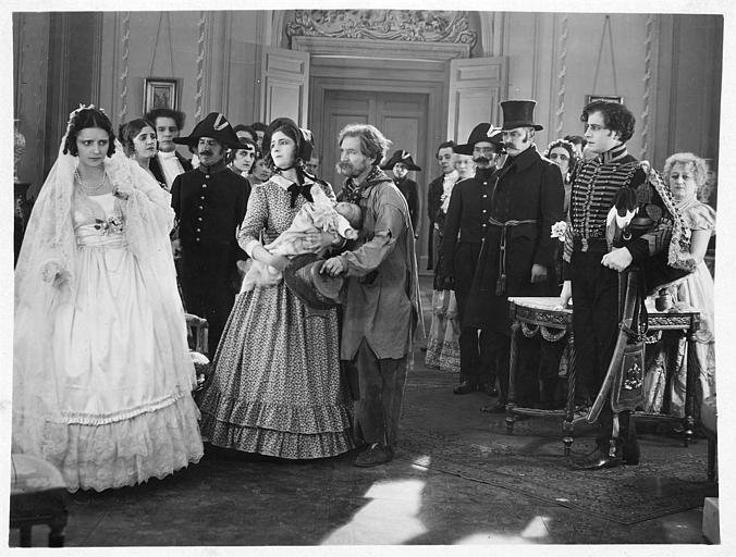 Dans un salon, entourée de personnages aristocratiques, Hélène Darly dans le rôle de Marie Didier en mariée au côté d'un homme et d'une femme portant un bébé dans 'Le chiffonnier de Paris' de Serge Nadejdine