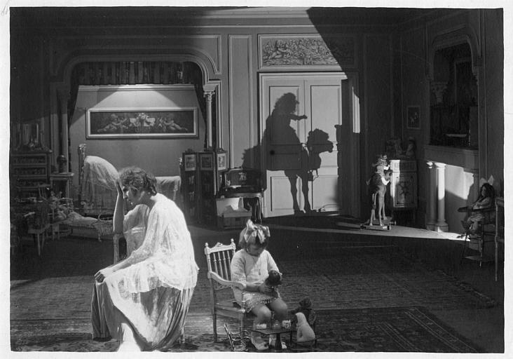 Dans une grande chambre, Hélène Darly et une enfant assises, avec l'ombre d'un chameau sur le mur