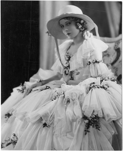 Portrait d'une femme assise portant une robe blanche à frou-frou et un chapeau