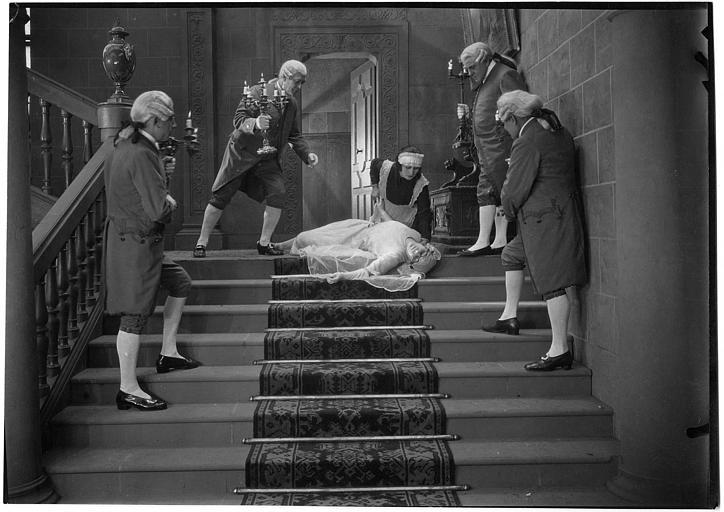 Nelly Muriel en robe de mariée, inanimée, en haut d'un escalier, entourée de son personnel dans 'Le mariage de minuit' d'Armand du Plessy
