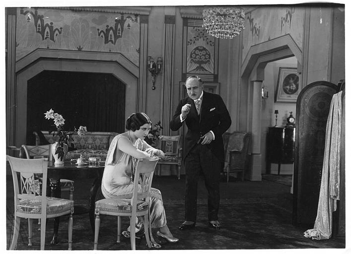 Une femme assise et un homme lui parlant dans un salon