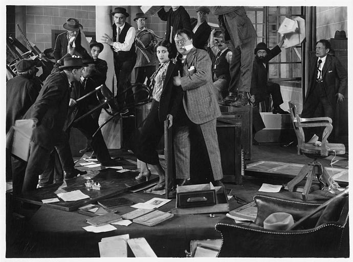 Un couple au milieu d'un bureau en train d'être saccagé par une dizaine d'hommes