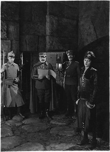 Une femme dans une cellule de prison avec trois soldats