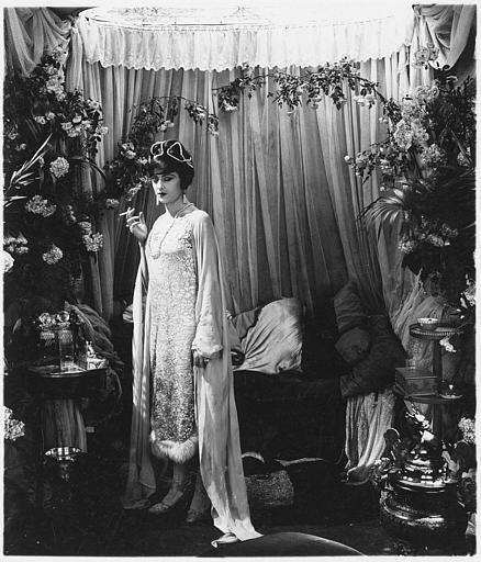 Une femme fumant une cigarette dans une chambre luxueuse
