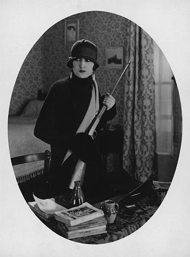Une femme portant un fusil dans une chambre