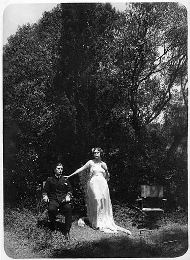 Nathalie Kovanko dans le rôle d'Hélène, debout, et un officier assis dans une chaise dans un jardin dans 'Jean d'Agrève' de René Leprince
